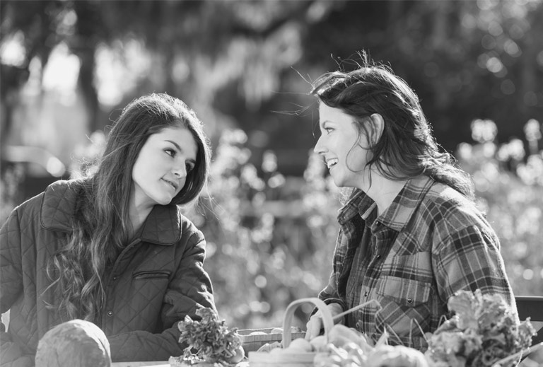 Black and white photo of a teen girl and older woman talking at a picnic