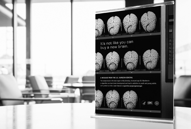 Black and white photo of Surgeon General print ad standing on a table in an office environment with desks in the background