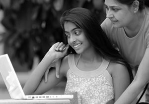 Black and white photo of a mother and daughter talking outside while looking at a laptop